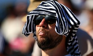 A spectator shields himself from the temperature at Wimbledon.