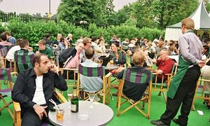 Visitors sit outside in green directors' chairs consuming on tennis championships